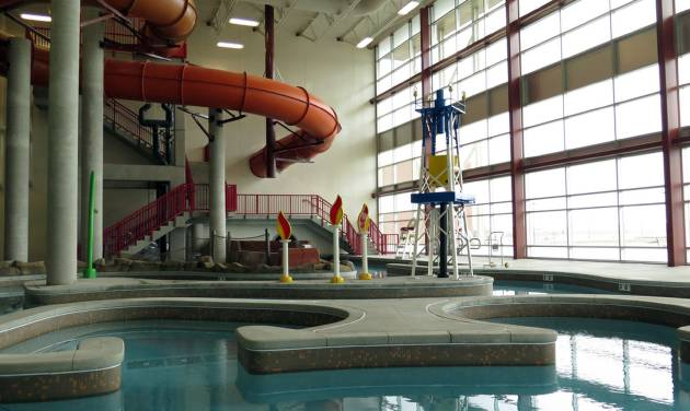 In this March 27, 2014 photo an oil derrickand the flames of gas fires decorate an indoor water park at a new recreation center in oil-rich Williston, North Dakota. The city hopes the center will help draw families to North Dakota's oil patch. (AP Photo/Josh Wood)