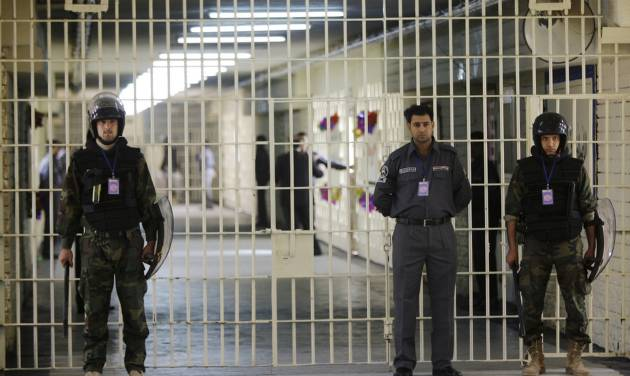 FILE - In this Feb. 21, 2009 file photo, guards stand at a cell block at the renovated Abu Ghraib prison, now renamed Baghdad Central Prison and run by Iraqis in Baghdad, Iraq. Late-night jailbreak attempts at two major prisons outside Baghdad have killed dozens, including at least 25 members of Iraq's security forces who battled militants armed with car bombs, mortars and machine guns, officials said Monday. (AP Photo/Karim Kadim, File)