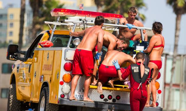 Lifeguards assist a person who was in the water and apparently struck by lightening Sunday July 27, 2014 in Los Angeles. Authorities said lightning struck 14 people, leaving two critically injured, as rare summer thunderstorms swept through Southern California on Sunday. (AP Photo/Steve Christensen)