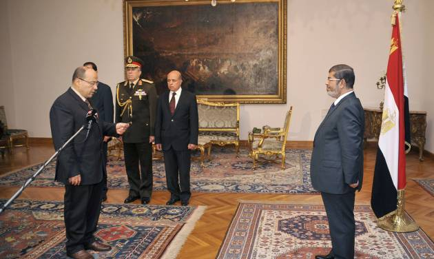 In this photo released by the Egyptian Presidency, President Mohammed Morsi, right, swears in his new Prosecutor General, Talaat Abdullah, left, in Cairo, Egypt, Thursday, Nov. 22, 2012. Egypt's president on Thursday issued constitutional amendments granting himself far-reaching powers and ordering the retrial of leaders of Hosni Mubarak's regime for the killing of protesters in last year's uprising. Morsi also on Thursday fired the country's top prosecutor by decreeing with immediate effect that he could only stay in office for four years and replacing him with Talaat Abdullah. Morsi fired Abdel-Maguid Mahmoud for the first time in October, but had to rescind his decision when he found that the powers of his office do not empower him to do so. (AP Photo/Egyptian Presidency