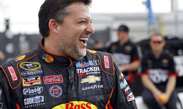 FILE - In this July 4, 2014, file photo, driver Tony Stewart laughs with several officials during qualifying for the NASCAR Sprint Cup Series auto race at Daytona International Speedway in Daytona Beach, Fla. Racing sprint cars is Stewart's passion. But now his hobby, racing on tiny little tracks in nondescript towns outside of a busy NASCAR schedule, is again being called into question. The three-time NASCAR champion struck and killed a 20-year-old racer who had climbed from his car Saturday, Aug. 9, to confront Stewart on a New York dirt track following a crash caused by contact between the two cars. (AP Photo/Terry Renna, File)