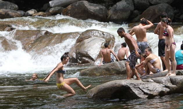 FILE - In this Thursday June 21, 2012 file photo, people find relief from the  heat as they play in the water at the Lower Falls of the Swift river in Albany, N.H. The popular spot along the Kancamagus Scenic Byway will be closed during the summer and fall of 2014 for renovations. (AP Photo/Jim Cole, File)