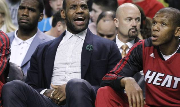 Miami Heat forward LeBron James yells at a referee while sitting on the bench in street clothes in the second half of the Heat's NBA basketball game against the Boston Celtics in Boston Wednesday, March 19, 2014. The Celtics won 101-96. (AP Photo/Elise Amendola)