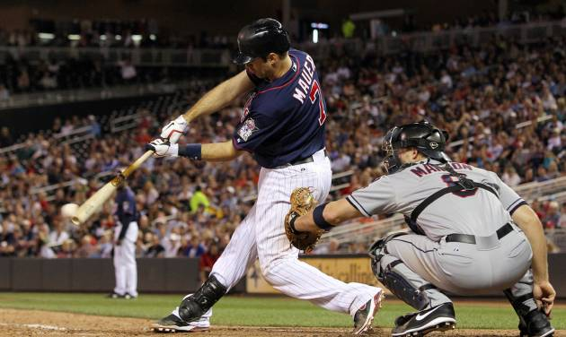 Minnesota Twins' Joe Mauer (7) hits an RBI single against Cleveland Indians relief pitcher Scott Maine as Indians catcher Lou Marson looks on during the seventh inning of a baseball game, Monday, Sept. 10, 2012, in Minneapolis. The Twins won 7-2. (AP Photo/Genevieve Ross)