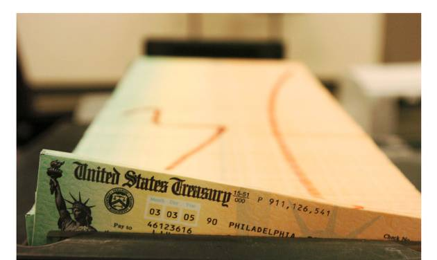 This two-photo combination image shows, at top, a Feb. 11, 2005 file photo of trays of printed social security checks waiting to be mailed from the U.S. Treasury's Financial Management services facility in Philadelphia, and an undated photo provided by the Treasury Department of a Direct Express Card. Starting next year, the check will no longer be put in the mail to millions of Americans who receive Social Security and other government benefits. The federal government, which issues 73 million payments a month, is phasing out paper checks for all benefit programs, requiring people to get payments electronically, either through direct deposit, or a debit card for those who don't have bank accounts. (AP Photo/Department of Treasury, File)