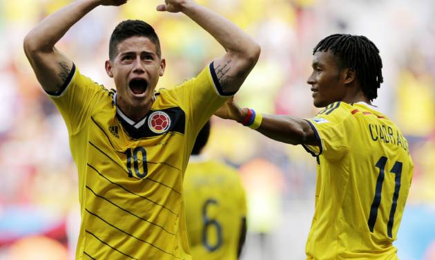 Colombia's James Rodriguez (10) celebrates with teammate Colombia's Juan Cuadrado after scoring his side's first goal during the group C World Cup soccer match between Colombia and Ivory Coast at the Estadio Nacional in Brasilia, Brazil, Thursday, June 19, 2014. (AP Photo/Fernando Llano)
