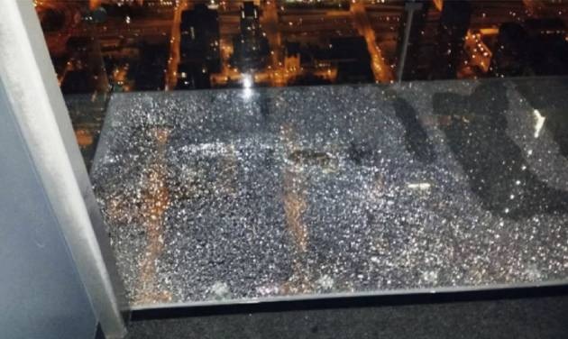 This Wednesday, May 28, 2014 photo provided by Alejandro Galibay shows the cracked coating of one of the glass bay of The Ledge, a popular tourist attraction on the 103rd story of the Willis Tower in Chicago. It started cracking when Galibay, of Stockton, Calif., his brother and two cousins, were sitting inside the transparent box. Garibay said Thursday, May 29, he knows now he wasn't in danger but when he first heard what sounded like breaking ice, he thought he was going to die. A statement from the building's management said the coating, which occasionally cracks, does not affect the structural integrity of the transparent ledge. (AP Photo/Alejandro Galibay)