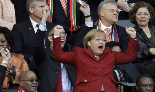 FILE - In this July 3, 2010 file photo German Chancellor Angela Merkel celebrates next to South African President Jacob Zuma, left, after Germany's Thomas Mueller scored a goal during the World Cup quarterfinal soccer match between Argentina and Germany at the Green Point stadium in Cape Town, South Africa. Merkel will travel to the World Cup final in Brazil _ giving Germany's most prominent fan perhaps her best chance yet to watch the team lift a trophy after eight years of steadfast support. President Joachim Gauck's office said Wednesday, July 9, 2014 that Gauck and Merkel will travel to Rio de Janeiro for the final against Argentina or the Netherlands.  (AP Photo/Gero Breloer, File)