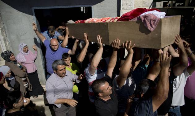 Relatives of Mohammed Krakra, an Israeli Arab teen, carry his coffin during his funeral at the northern Israeli Arab village of Arabeh, Israel, Monday, June 23, 2014. Israeli warplanes bombed the Syrian military headquarters and a number of other targets inside Syria, the Israeli military said Monday, in a blistering response to a cross-border attack that killed Krakra the previous day. (AP Photo/Oded Balilty)