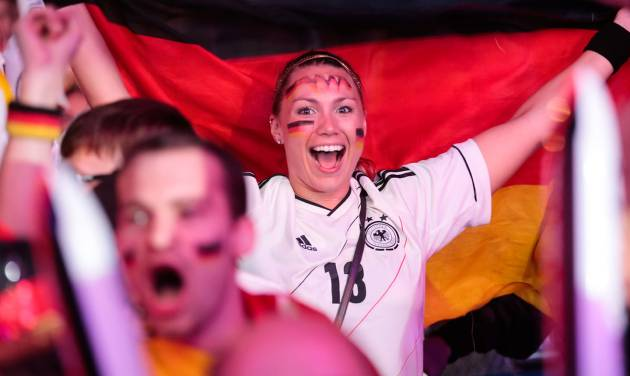 German soccer fans celebrate after their team scores at the Brazil World Cup semi final being played in Belo Horizonte, Brazil, between Germany and Brazil at a public viewing event called 'Fan Mile' in Berlin, Tuesday, July 8, 2014. (AP Photo/Markus Schreiber)
