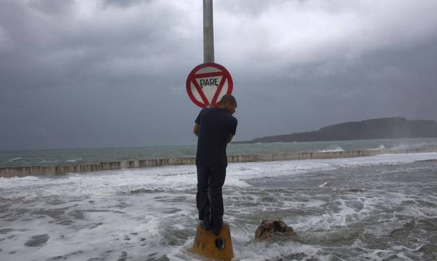 A man stands on a post with a stop sign as waves pass the seawall during the passage of Tropical Storm Isaac in Baracoa, Cuba, Saturday, Aug. 25, 2012. Tropical Storm Isaac pushed into Cuba on Saturday after sweeping across Haiti's southern peninsula. Isaac's center made landfall just before midday near the far-eastern tip of Cuba. (AP Photo/Ramon Espinosa)