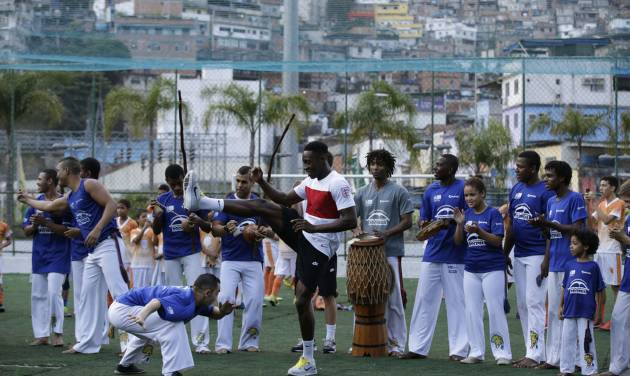 England national soccer team player Danny Welbeck, center, joins in a Capoeira dance demonstration with locals during a visit by a five England players to the Rocinha Sports Complex on the edge of the Rocina favela in Rio de Janeiro, Brazil, Monday June 9, 2014.  The England soccer team are staying in Rio de Janeiro as their base city for the 2014 soccer World Cup.  (AP Photo/Matt Dunham)