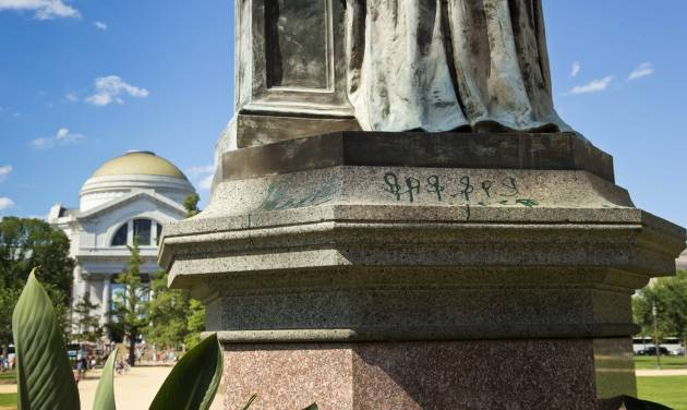 Green paint is seen on the pedestal of the statue of Joseph Henry, outside the headquarters of the Smithsonian Institution on the National Mall in Washington, Monday, July 29, 2013. U.S. Park police say the marring of the Smithsonian's first secretary was discovered on July 26, the same day that the Lincoln Memorial was splattered with green paint. The Smithsonian's Museum of Natural History is seen in the distance.  (AP Photo/J. Scott Applewhite)