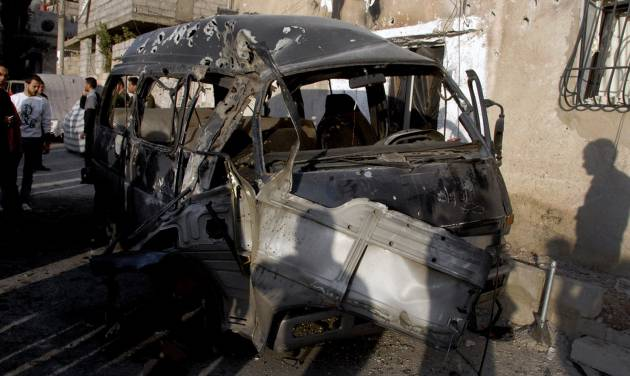 This photo released by the Syrian official news agency SANA, shows Syrians standing near a damaged vehicle at the scene after an attack in Damascus, Syria, Wednesday, Nov. 7, 2012. (AP Photo/SANA)