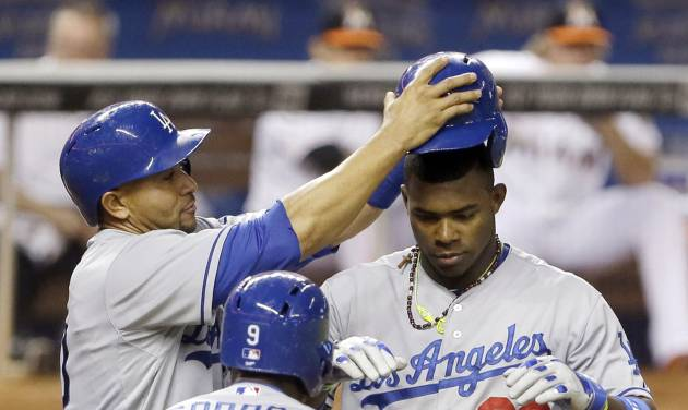 Los Angeles Dodgers' Yasiel Puig (66) celebrates with teammates Dee Gordon (9) and Miguel Olivo, rear left, after hitting a three-run home run, scoring them all, during the fourth inning of a baseball game against the Miami Marlins, Saturday, May 3, 2014, in Miami. (AP Photo/Wilfredo Lee)