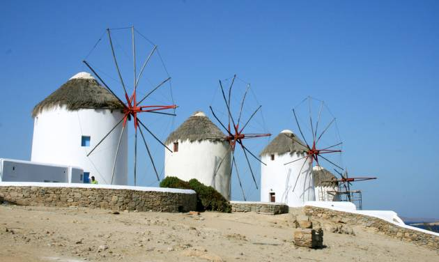 This July 6, 2014 photo shows picturesque windmills on the island of Mykonos in the Cyclades, a Greek island chain in the Aegean Sea. The tradition of building windmills on the island dates back centuries. The Cyclades are known for panoramic views of the sea, homes tucked into cliffsides and waterfronts, black-sand beaches and dramatic sunsets. (AP Photo/Kristi Eaton)