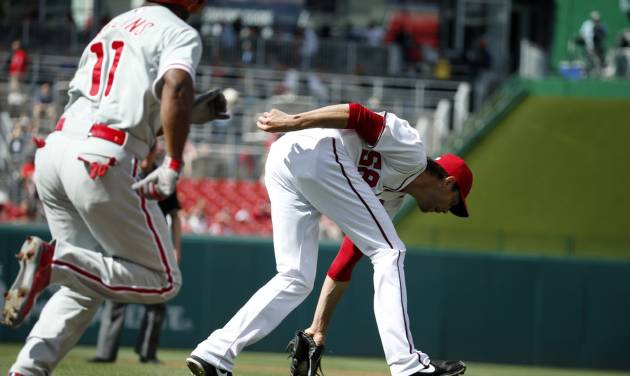 Washington Nationals starting pitcher Doug Fister (58) fields the sacrifice bunt by Philadelphia Phillies' Jimmy Rollins (11), who was out at first base on the play, during the first inning of a baseball game at Nationals Park Thursday, June 5, 2014, in Washington. (AP Photo/Alex Brandon)