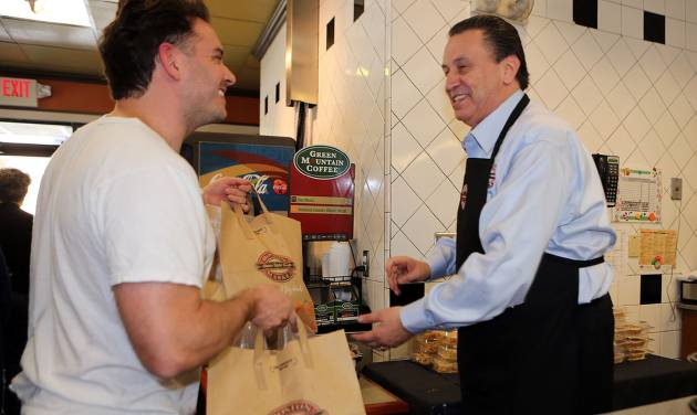 This Nov. 22, 2012 photo provided by Boston Market shows Boston Market CEO George Michel, right, working inside a company's Miami-area restaurant on the home style restaurant chains busiest day of the year, Thanksgiving, in Miami. Boston Market Corp. is reporting record Thanksgiving sales this year, and it's already planning for next Thanksgiving. The Golden, Colo.-based restaurant chain had not yet released specific dollar figures but said total sales per restaurant from Nov. 19 to Nov. 23 were up 13 percent from a comparable period last year. (AP Photo/Boston Market, Marc Serota)