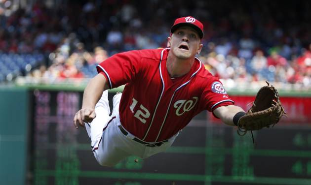 Washington Nationals first baseman Tyler Moore makes a diving catch for the out on a foul ball hit by New York Mets' Eric Young Jr. during the first inning of a baseball game at Nationals Park Sunday, May 18, 2014, in Washington. (AP Photo/Alex Brandon)