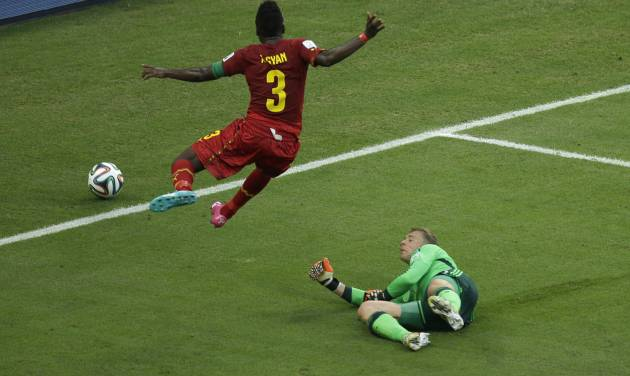 Ghana's Asamoah Gyan, left, leaps as he runs past Germany's goalkeeper Manuel Neuer during the group G World Cup soccer match between Germany and Ghana at the Arena Castelao in Fortaleza, Brazil, Saturday, June 21, 2014. (AP Photo/Themba Hadebe)