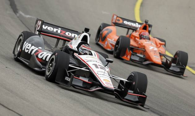 Will Power (12) races Simon Pagenaud, right, during practice for the IndyCar Series' Iowa Corn Indy 300 auto race, Friday, July 11, 2014, at Iowa Speedway in Newton, Iowa. (AP Photo/Charlie Neibergall)