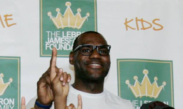"""NBA star and Akron native LeBron James and his mother Gloria James, right, pose with children participating in the LeBron James Family Foundation's Wheels for Education """"Time to Promise"""" School Year event at Canal Park during an Akron Aeros game Sunday, Aug. 19, 2012 in Akron, Ohio. (AP Photo/Akron Beacon Journal, Karen Schiely) MANDATORY CREDIT"""