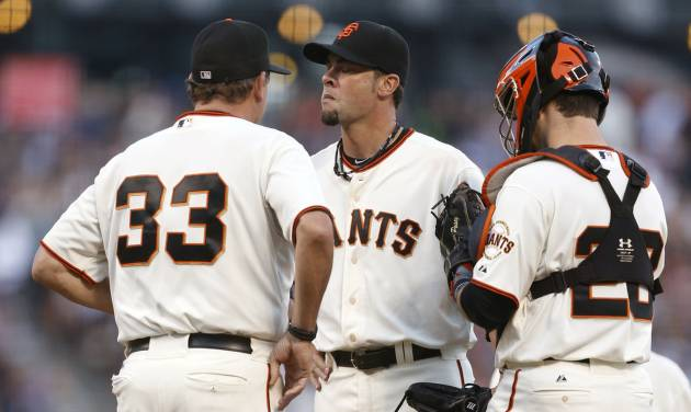 San Francisco Giants pitcher Ryan Vogelsong, center, receives a visit from pitching coach Dave Righetti (33) and catcher Buster Posey during the sixth inning of a baseball game against the Los Angeles Dodgers, Saturday, July 26, 2014, in San Francisco. (AP Photo/Beck Diefenbach)