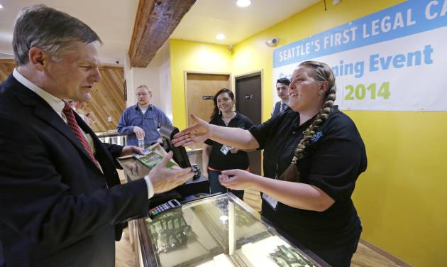 Seattle City Attorney Pete Holmes, left, shakes hands with clerk Pam Fenstermacher after purchasing marijuana at Cannabis City, Tuesday, July 8, 2014, in Seattle, on the first day that sales of recreational pot became legal in the state.  Washington on Tuesday became the second state to allow people to buy marijuana legally in the U.S. without a doctor's note as eager customers who lined up outside stores made their purchases and savored the moment. (AP Photo/Elaine Thompson, Pool)