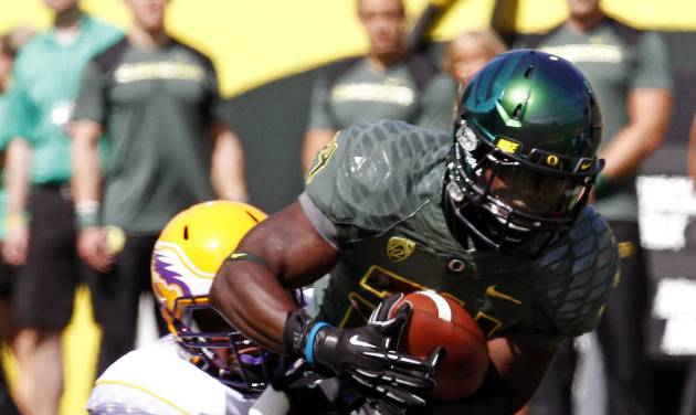 Oregon running back Kenjon Barner, right, fights for yardage against Tennessee Tech defender Howard Griffin during the first half of their NCAA college football game in Eugene, Ore., Saturday, Sept. 15, 2012. (AP Photo/Don Ryan)