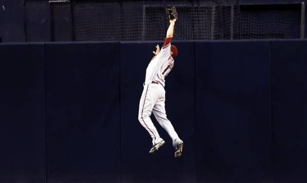 Arizona Diamondbacks center fielder A.J. Pollock makes a leaping catch at the wall, robbing San Diego Padres' Rene Rivera of a hit, during the third inning of a baseball game Thursday, Sept. 4, 2014, in San Diego. (AP Photo/Gregory Bull)