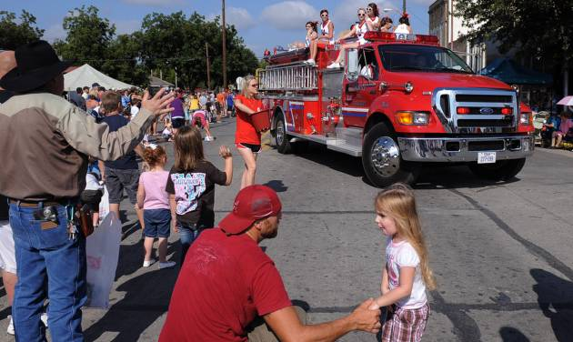In this Sept. 1, 2012 photo, a volunteer fire department truck turns the corner during the annual Westfest parade in West, Texas. Starting Friday, Aug. 30, 2013, the town will hold the signature celebration of its Czech heritage - the first Westfest since a deadly fertilizer plant explosion tore through the small Central Texas community in April 2013. (AP Photo/Waco Tribune Herald, Rod Aydelotte)