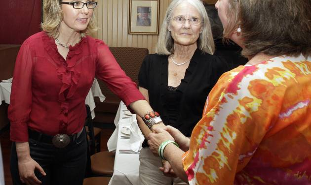 In this photo taken Friday, July 5, 2013, former Arizona Rep. Gabrielle Giffords greets Jackie Barden, right, mother of a Sandy Hook Elementary School shooting victim Daniel Barden, as local supporter Mary Ann Sosnoff, center, looks on at the Orchard Street Chop Shop in Dover, N.H.  Three years after being shot in the head, Giffords is in New Hampshire to urge support for background checks on gun purchases. (AP Photo/Mary Schwalm)