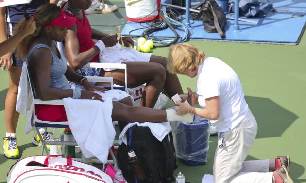 Serena Williams, left, has her angle re-taped as Venus Williams looks on during a break between games during a quarterfinals doubles match against Elena Vesnina and Ekaterina Makarova at the 2014 U.S. Open tennis tournament, Tuesday, Sept. 2, 2014, in New York. (AP Photo/John Minchillo)
