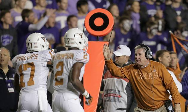 Texas coach Mack Brown, right, celebrates with cornerback Adrian Phillips (17) and defensive back Mykkele Thompson (2) after Phillips intercepted a pass during the first half of an NCAA college football game against Kansas State, Saturday, Dec. 1, 2012, in Manhattan, Kan. (AP Photo/Charlie Riedel)