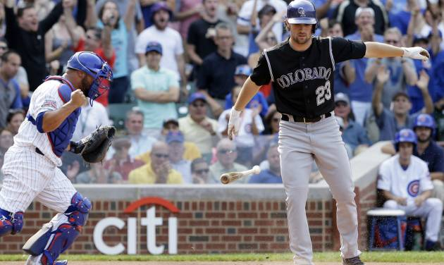 Colorado Rockies' Charlie Culberson, right, throws his bat after being called out on strikes as Chicago Cubs catcher Welington Castillo celebrates during the ninth inning of a baseball game in Chicago, Thursday, July 31, 2014. The Cubs won 3-1. (AP Photo/Nam Y. Huh)