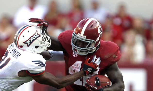 Alabama running back Eddie Lacy (42) stiff-arms Florida Atlantic defensive back D'Joun Smith (21) and runs for a first down during the first half of a NCAA college football game on Saturday, Sept. 22, 2012, in Tuscaloosa, Ala. (AP Photo/Butch Dill)