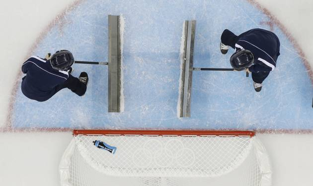 Volunteers refresh the ice during a break in the action at the 2014 Winter Olympics women's ice hockey game between Japan and Germany at Shayba Arena, Thursday, Feb. 13, 2014, in Sochi, Russia. (AP Photo/Matt Slocum)