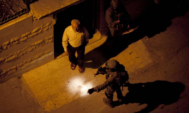 Israeli soldiers arrest Abdel Aziz Dweik, speaker of the long-defunct Palestinian parliament and a senior Hamas figure, at his home during a military operation to search for three missing Israeli teenagers, in the West Bank city of Hebron, Monday, June 16, 2014. Israel continued its sweep of arrests in the West Bank early Monday, rounding up senior Hamas figures and other Palestinians in a feverish search for three missing Israeli teenagers who Israel says Hamas kidnapped, as Israel's government considered punitive actions against the militant Palestinian group. (AP Photo/Majdi Mohammed)