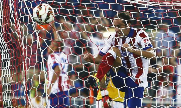 Atletico's Diego Godin, from Uruguay celebrates Joao Miranda's goal during a Spanish La Liga soccer match between Atletico de Madrid and Eibar at the Vicente Calderon stadium in Madrid, Spain, Saturday, Aug. 30, 2014. (AP Photo/Andres Kudacki)
