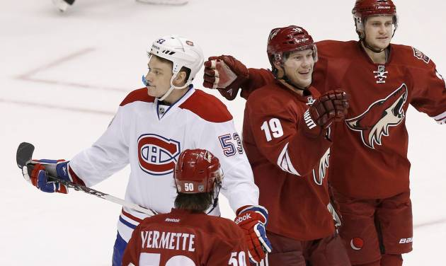 Phoenix Coyotes' Shane Doan (19) celebrates his goal with teammates Antoine Vermette (50) and Oliver Ekman-Larsson (23), of Sweden, as Montreal Canadiens' Ryan White (53) skates past during the third period of an NHL hockey game on Thursday, March 6, 2014, in Glendale, Ariz.  The Coyotes defeated the Canadiens 5-2. (AP Photo/Ross D. Franklin)