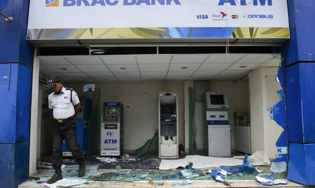A security guard walks near ATM machines damaged by Islamic hardliners in Savar near Dhaka, Bangladesh, Monday, May 6, 2013. At least 15 people died in clashes Monday between police and Islamic hardliners demanding that Bangladesh implement an anti-blasphemy law, police said. (AP Photo/Ismail Ferdous)