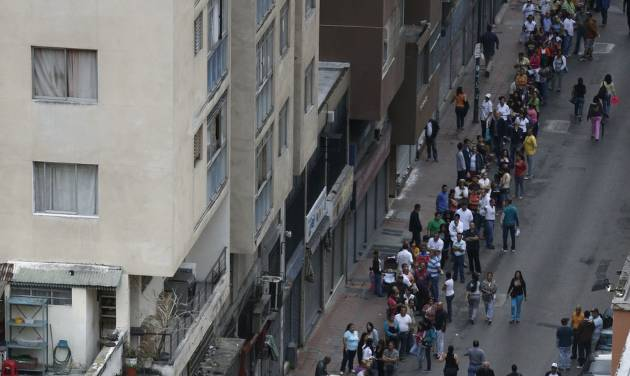 Residents line up at a polling station to vote in presidential elections in Caracas, Venezuela, Sunday, Oct. 7, 2012. President Hugo Chavez is running against opposition candidate Henrique Capriles.(AP Photo/Fernando Llano)
