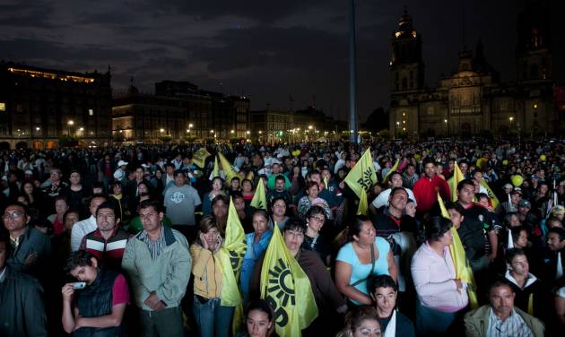 People watch the first televised presidential debate at Mexico City's main Zocalo plaza, Sunday, May 6, 2012. Next July 1, Mexico will hold presidential elections. (AP Photo/Eduardo Verdugo)