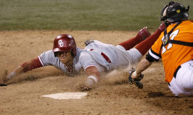 OU's Hector Lorenzana, left, slides home past OSU's Gage Green in the 18th inning of the Sooners' 12-9 nonconference win on Tuesday night is Stillwater.                                                                             Photo by Bryan Terry, The Oklahoman