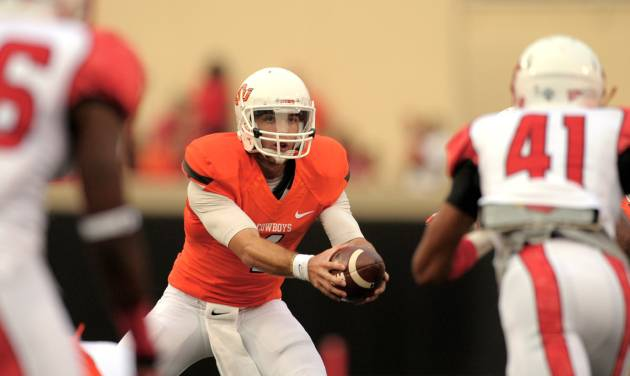 Oklahoma State quarterback J.W. Walsh, center, watches the advance of Lamar linebacker Jestin White, right, prior to completing a handoff to a teammate during the first half of an NCAA college football game in Stillwater, Okla., Saturday, Sept. 14, 2012. (AP Photo/Brody Schmidt) ORG XMIT: OKBS105
