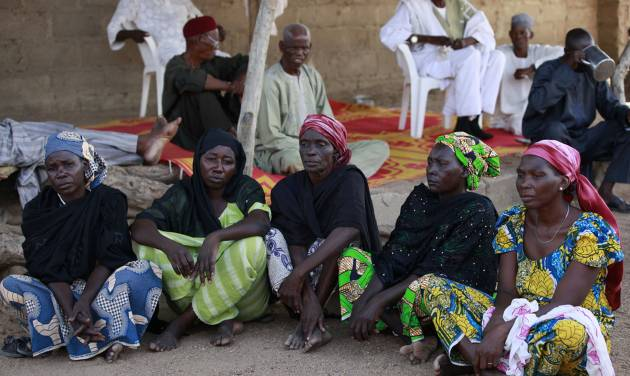 FILE- In this Sunday, May 18, 2014 file photo some of the parents of the kidnapped school girls sit outside a compound during a meeting in Chibok, Nigeria. At least 11 parents of the more than 200 kidnapped Nigerian schoolgirls will never see their daughters again. Since the mass abduction of the schoolgirls by Islamic extremists three months ago, at least 11 of their parents have died and their hometown, Chibok, is under siege from the militants, residents report. Seven fathers of kidnapped girls were among 51 bodies brought to Chibok hospital after an attack on the nearby village of Kautakari this month, said a health worker who insisted on anonymity for fear of reprisals by the extremists. At least four more parents have died of heart failure, high blood pressure and other illnesses that the community blames on trauma due to the mass abduction 100 days ago, said community leader Pogu Bitrus, who provided their names.  (AP Photo/Sunday Alamba, File)