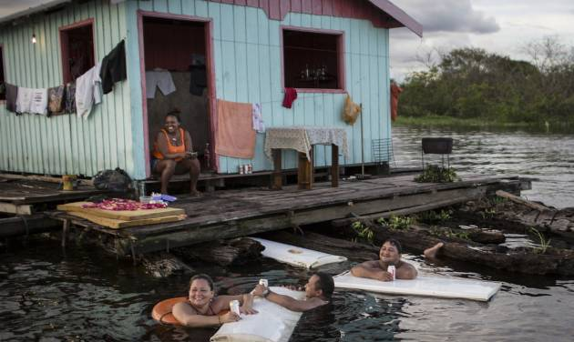 In this May 18, 2014 photo, residents use refrigerator doors as floating tables outside their floating house on the Rio Negro in Cacau Pirera, near Manaus, Brazil. A World Cup host city, Manaus' far-flung location in the heart of the world's biggest rainforest makes it reachable only by plane or boat. Thousands of foreigners are expected to begin arriving in the Amazonian metropolis for the international soccer matches being held in Manaus's new multi-million dollar soccer stadium. (AP Photo/Felipe Dana)
