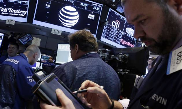 Traders gather at the post that handles AT&T on the floor of the New York Stock Exchange Monday, May 19, 2014. Priming itself for the age of Internet-delivered video, AT&T Inc. said it would buy DirecTV for $48.5 billion in cash and stock, or $95 per share. (AP Photo/Richard Drew)