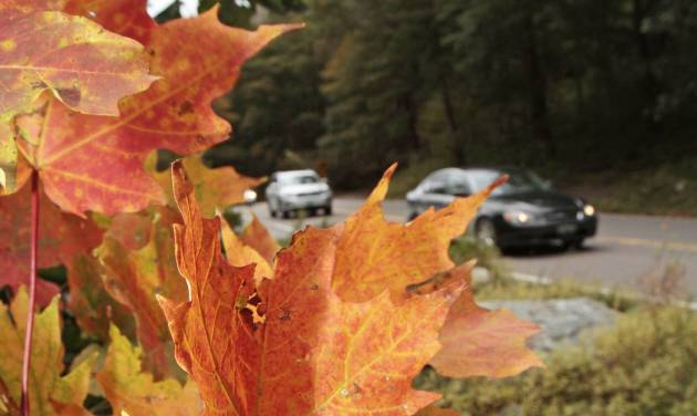 In this Sept. 16, 2011 photo, autos drive by colorful foliage in Smugglers Notch in Stowe, Vt. Mountain and lake views along with fall foliage can be had for free in Vermont's largest city of Burlington, which feels more like a big town than a city. (AP Photo/Toby Talbot)
