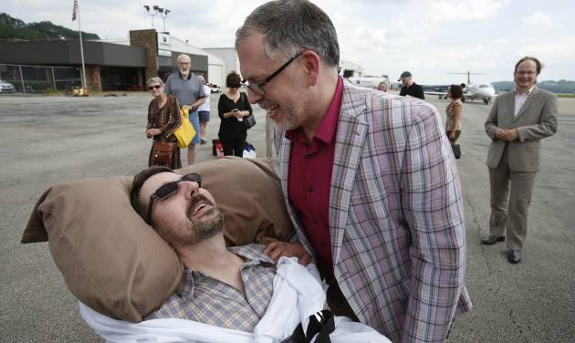 This photo made Thursday, July 11, 2013, shows Jim Obergefell, right, and John Arthur after they returned from their wedding flight at Landmark Aviation at Cincinnati's Lunken Airport. The couple were married during a short ceremony on the plane, on the tarmac, at Baltimore/Washington International Thurgood Marshall Airport, after flying in from Cincinnati.  John suffers from ALS, is bed-ridden, and is now in hospice care. A federal judge has ruled in favor of the two Ohio men who want their out-of-state marriage recognized John nears death, a case that's seen as encouraging for same-sex marriage supporters in Ohio. (AP Photo/The Cincinnati Enquirer, Gary Landers) MANDATORY CREDIT, NO SALES